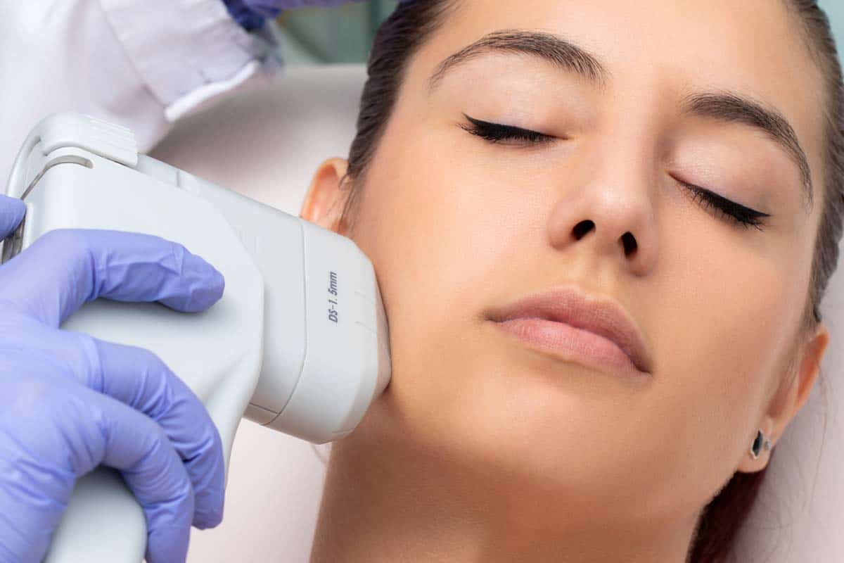 Top view of woman having cosmetic facial high intensity focal ultrasound treatment.